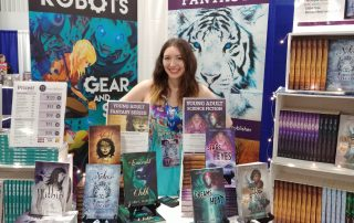 Clare at Ottawa Comiccon 2019 behind her table of books